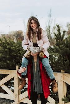 Una giovane donna siede sulle spalle di un uomo sullo sfondo degli alberi di natale
