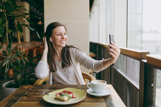 Giovane donna seduta da sola nella caffetteria a tavola con una tazza di cappuccino, torta, rilassante al ristorante durante il tempo libero. giovane donna che fa selfie sul cellulare, riposa nella caffetteria. concetto di stile di vita.