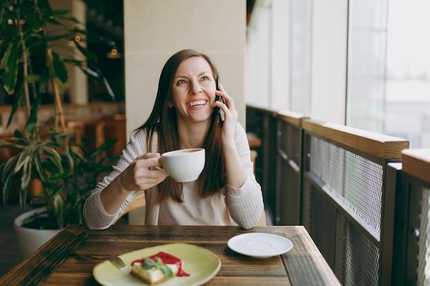 Giovane donna seduta da sola nella caffetteria a tavola con una tazza di cappuccino, torta, rilassante al ristorante durante il tempo libero. giovane femmina parlando al telefono cellulare, riposando nella caffetteria. concetto di stile di vita.