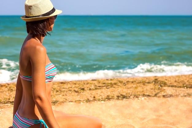 Giovane donna seduta sulla spiaggia guardando il mare e il cielo estivo sfondo con spazio copia
