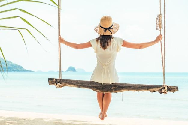 Giovane donna seduta su un'altalena sulla spiaggia. felice donna viaggiatrice. concetto di vacanza