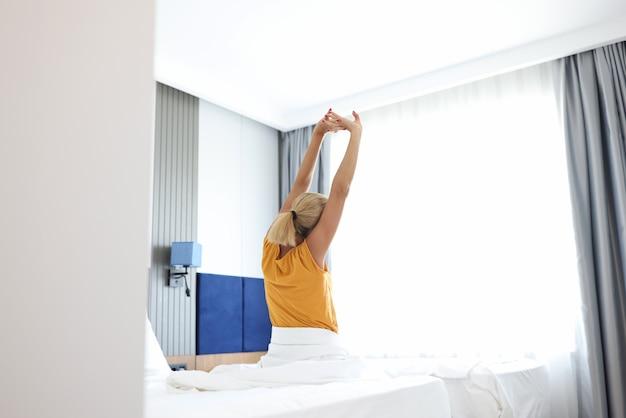 Giovane donna seduta sul letto e allungando la vista posteriore