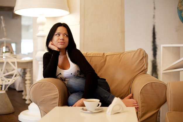 Giovane donna che si siede in un caffè che beve caffè