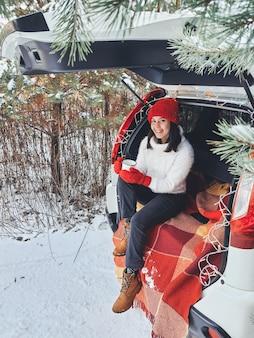 Giovane donna seduta nel bagagliaio dell'auto bevendo tè caldo al giorno di neve invernale