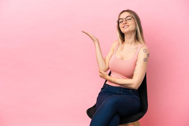Giovane donna seduta su una sedia su sfondo rosa isolato che estende le mani di lato per invitare a venire