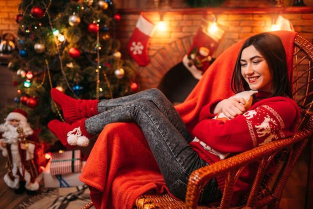 Giovane donna seduta su una sedia vicino al camino, albero di natale con decorazioni, celebrazione delle vacanze di natale