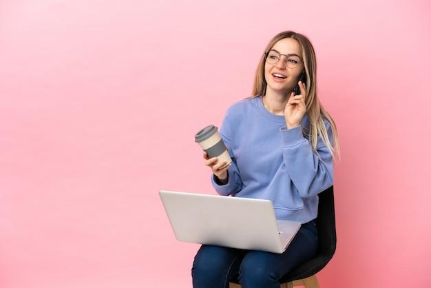 Giovane donna seduta su una sedia con un computer portatile su sfondo rosa isolato che tiene caffè da portare via e un cellulare