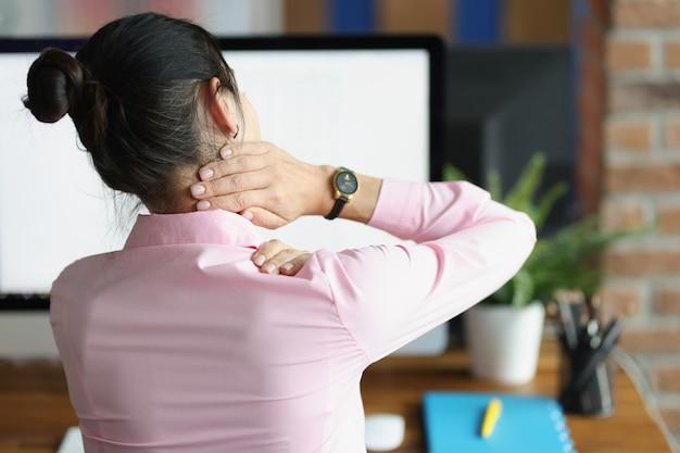 Giovane donna seduta al computer e tenendo il collo dolorante con la mano vista posteriore sedentaria