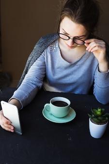 Giovane donna seduta in tavola calda con una tazza di caffè