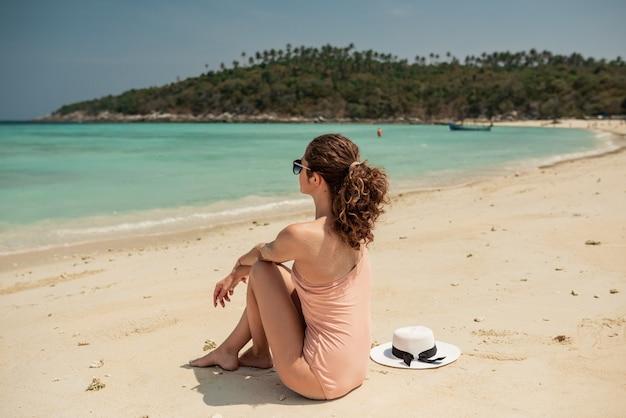 Giovane donna seduta e godendo della libertà sulle montagne più alte in una giornata di sole.