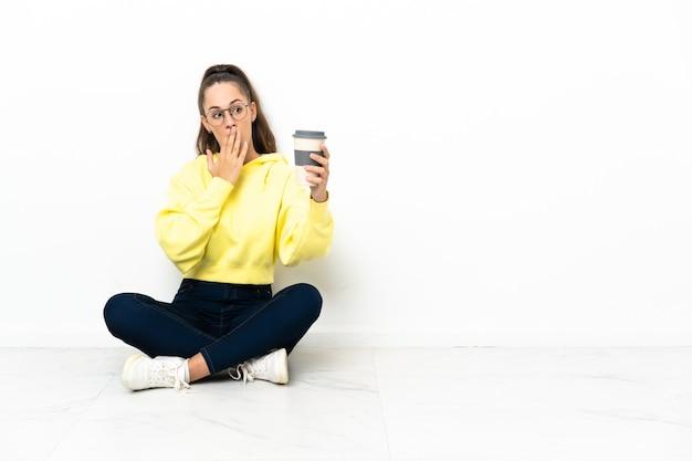 Giovane donna seduta sul pavimento con in mano un caffè da asporto con sorpresa e scioccata espressione facciale