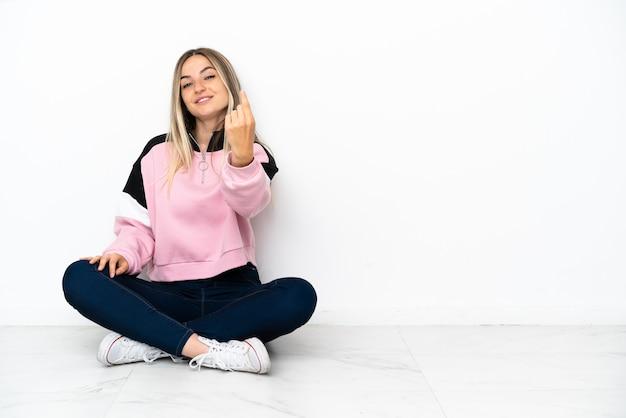 Giovane donna seduta sul pavimento al chiuso che fa un gesto imminente