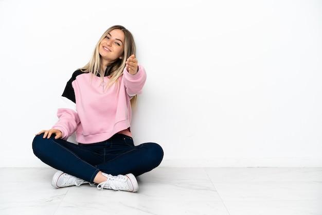 Giovane donna seduta sul pavimento in casa che stringe la mano per aver chiuso un buon affare