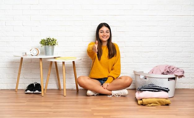 Giovane donna seduta sul pavimento in interni con cesto di vestiti che agitano le mani per chiudere un buon affare