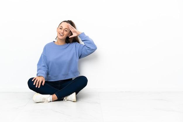Giovane donna seduta sul pavimento salutando con la mano con felice espressione