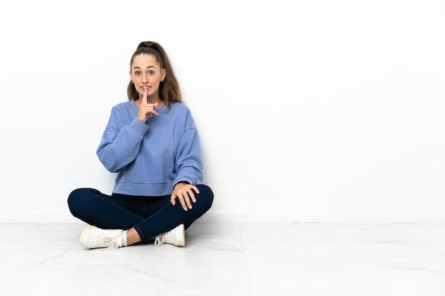 Giovane donna seduta sul pavimento che mostra un segno di gesto di silenzio mettendo il dito in bocca