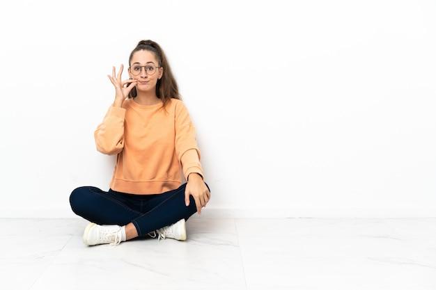 Giovane donna seduta sul pavimento che mostra un segno di gesto di silenzio
