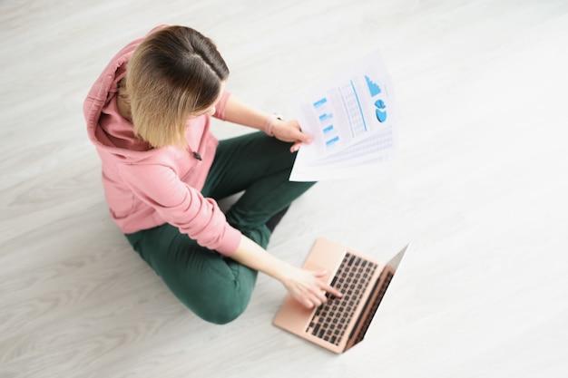 Giovane donna seduta sul pavimento con documenti in mano e lavorando alla vista dall'alto del computer portatile. concetto di lavoro a distanza a casa