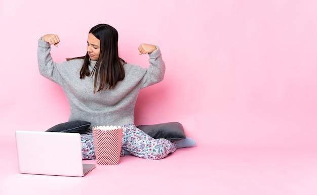 Giovane donna seduta sul pavimento con un computer portatile