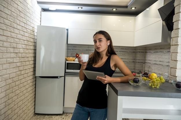 Giovane donna seduta davanti al computer portatile aperto e beve caffè nella sua cucina. godendo il tempo a casa