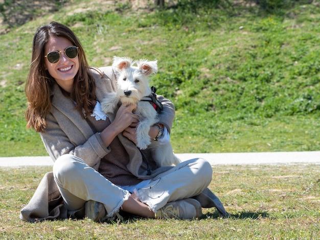 Giovane donna seduta per terra nel campo, che gioca e sorride con il suo cucciolo di schnauzer bianco.