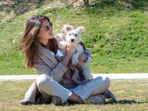 Giovane donna seduta per terra nel campo, trascorrendo del tempo con il suo cucciolo di schnauzer bianco.