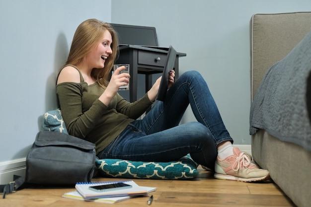 Giovane donna seduta a casa sul pavimento con tavoletta digitale e bicchiere d'acqua. la ragazza studia, legge, riposa usando internet