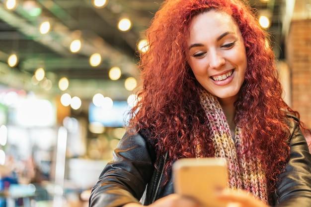 Giovane donna seduta al coperto in un caffè urbano alla moda che scrive con il suo telefono cellulare.