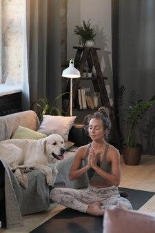 Giovane donna seduta nella posizione del loto con gli occhi chiusi e rilassante durante la meditazione a casa