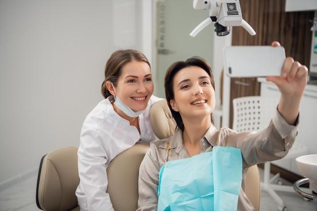 Giovane donna seduta in un centro di odontoiatria medica, prendendo un selfie con il suo smartphone