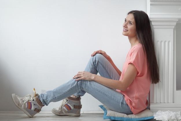 Giovane donna seduta vicino al camino in un soggiorno moderno.