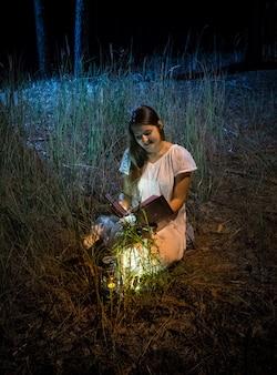 Giovane donna seduta di notte nella foresta con lanterna che legge un grande vecchio libro