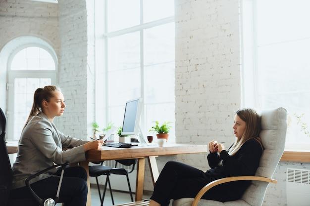 Giovane donna seduta in ufficio durante il colloquio di lavoro con impiegata, capo o responsabile delle risorse umane, parlare, pensare, sembra sicura. concetto di lavoro, lavoro, affari, finanza, comunicazione.