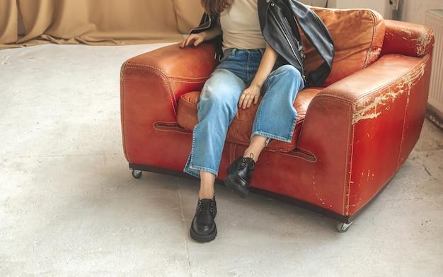 Giovane donna seduta su una vecchia poltrona in pelle in interni di studio, abiti casual e urbani e foto di moda