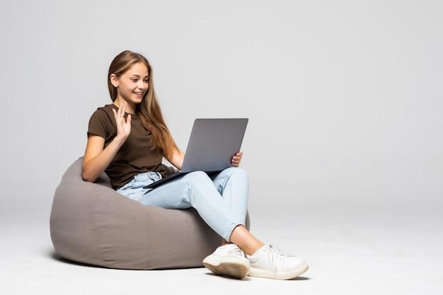 La giovane donna che si siede sul pufff con il computer portatile effettua la videochiamata isolata sulla parete bianca