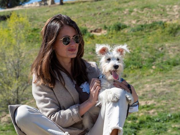 Giovane donna seduta su una roccia in un campo, in posa per una foto con il suo cucciolo di schnauzer bianco.
