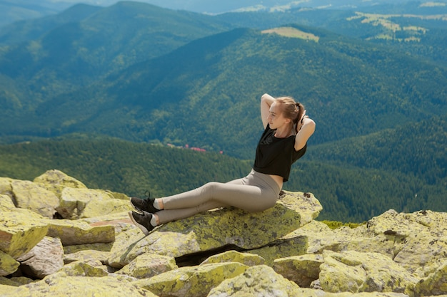 Giovane donna seduta su una roccia e guardando verso l'orizzonte.