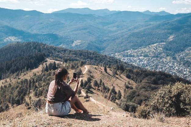 Giovane donna seduta su una roccia con zaino e guardando l'orizzonte