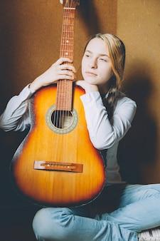 Giovane donna che si siede nella sala sul pavimento e suonare la chitarra a casa