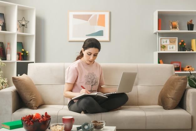 Giovane donna seduta sul divano dietro il tavolino da caffè che tiene e usa il laptop leggendo sul libro in soggiorno
