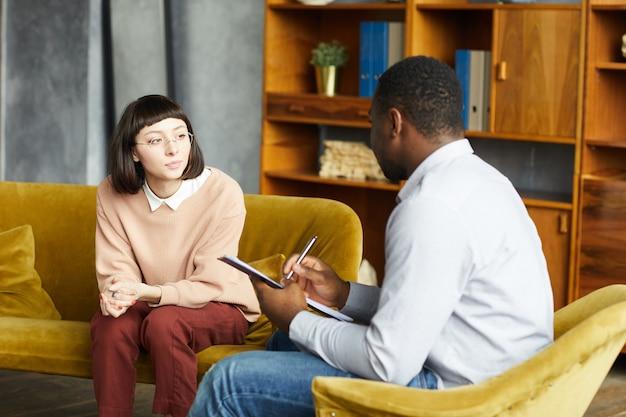Giovane donna seduta sul divano e parlando con l'uomo africano mentre prende appunti nel documento in ufficio