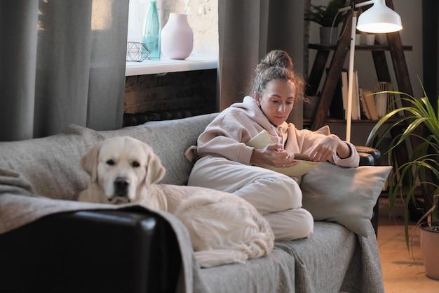 Giovane donna seduta sul divano con il suo cane e leggere un libro durante il suo tempo libero a casa