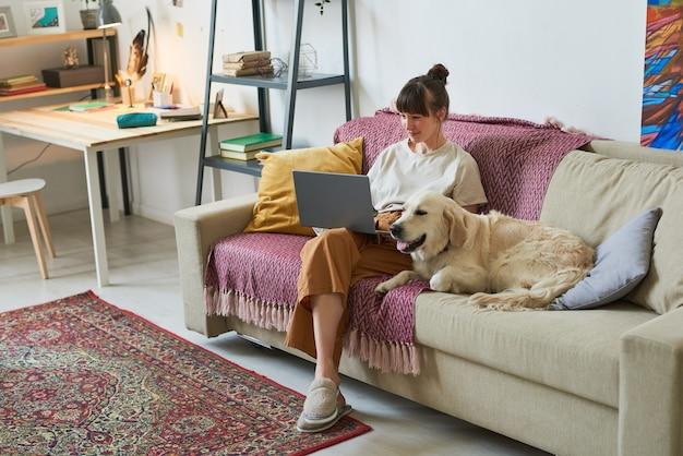 Giovane donna seduta sul divano con il suo cane e che lavora al laptop online a casa