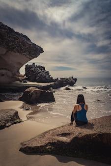 Giovane donna seduta su una pietra sulla spiaggia che guarda al mare