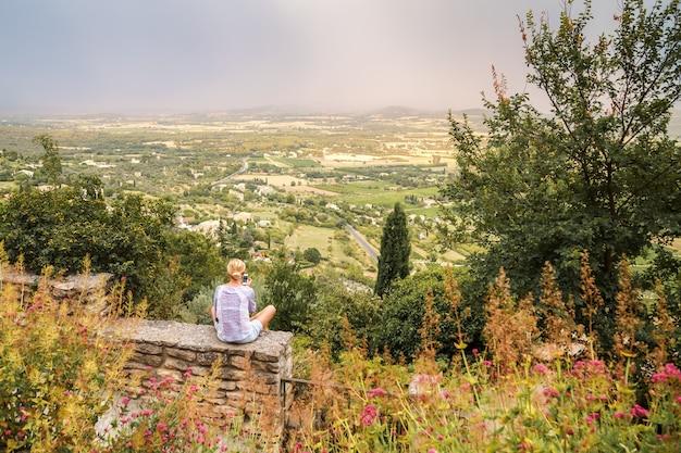 Giovane donna seduta sul recinto di pietra nel borgo medievale sulla collina di gordes provence france