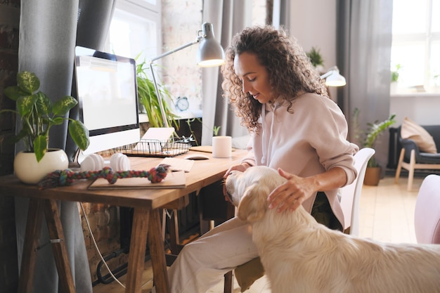 Giovane donna seduta al tavolo davanti al computer a casa e nutrire il suo cane