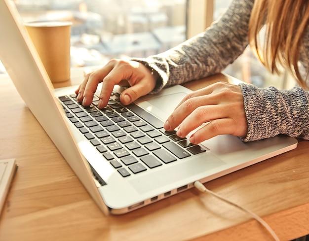 Giovane donna seduta a tavola e lavora con il suo laptop moderno
