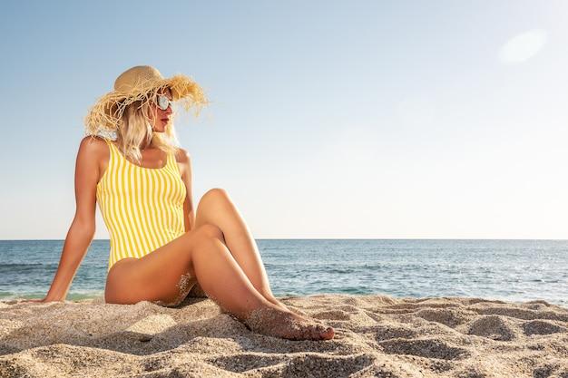 Giovane donna seduta su una spiaggia tropicale.