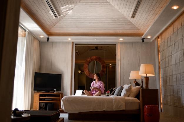 Giovane donna che si siede con il letto della tazza di caffè nell'interno moderno della camera da letto con, tv, computer portatile e altre decorazioni di modo. camera da letto moderna rilassamento dopo giorni lavorativi segno bluetooth