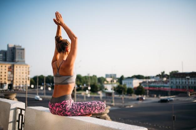 Giovane donna seduta in posa yoga, città. yogi che si allena all'aperto, esercizio di rilassamento